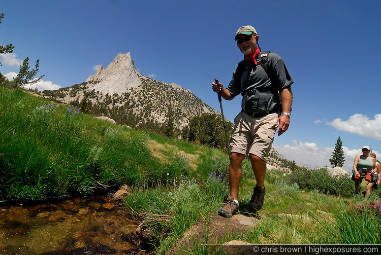 Hikers walk along a creek below Cathedral Peak in Yosemite.