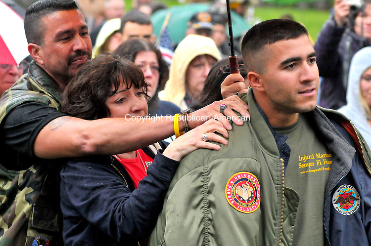 WOLCOTT, CT-16 APRIL 2010-041610JS11- U.S.M.C. Cpl. Luis Hernandez Jr., stands with his mother Mary Hernandez and father Luis Hernandez Sr., as he in introduced during his welcome home celebration in Wolcott on Friday. Cpl. Hernandez was returning home after being seriously injured by an IED while serving in Afghanistan on April 4. <br /> Jim Shannon Rep-Am