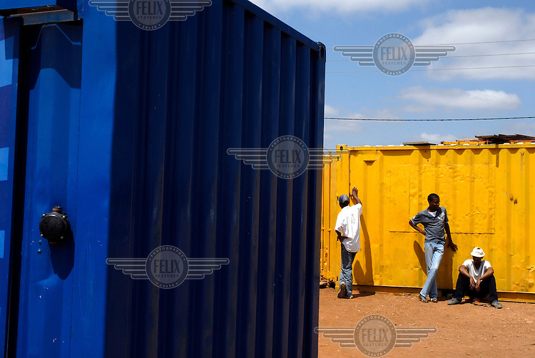 Unemployed young men wait for an offer of casual labour next to businesses that are trading out of converted shipping containers.