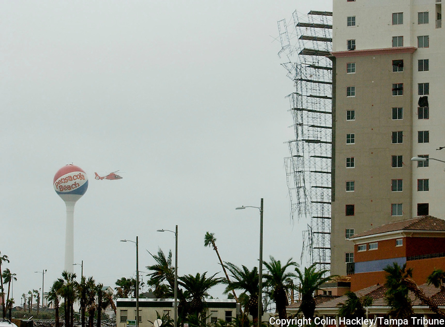 Pensacola Beach, Fl. 7/10/05-A Coast Guard helicopter flies over Pensacola Beach after Hurricane Dennis swept through Sunday. Dennis peeled the scaffolding off of the South Harbor condominium building at right. COLIN HACKLEY PHOTO
