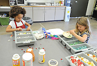NWA Democrat-Gazette/MICHAEL WOODS • @NWAMICHAELW<br /> Naomi Yayock, 6, (left) and Sagely Ward, 7, looks for tiles as they work on creating mosaic flower pots Wednesday, March 23, 2016, during  the Spring Break Camp at the Community Creative Center in Fayetteville.  The spring break camp gave kids a chance to create colorful art  inspired by the joyfulness of Spring with activities including watercolor painting, drawing with soft pastels, mosaic sculptures, and mosaic flower pots for the garden.