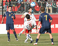 Graham Zusi #11 and Doug Rodkey #5 of the University of Maryland send the ball past Andrew Wiedeman #3 and Davis Paul #7 of the University of California during an NCAA championship round of sixteen soccer match at Ludwig Field, on November 29, 2008 in College Park, Maryland. The match was won by Maryland 2-1