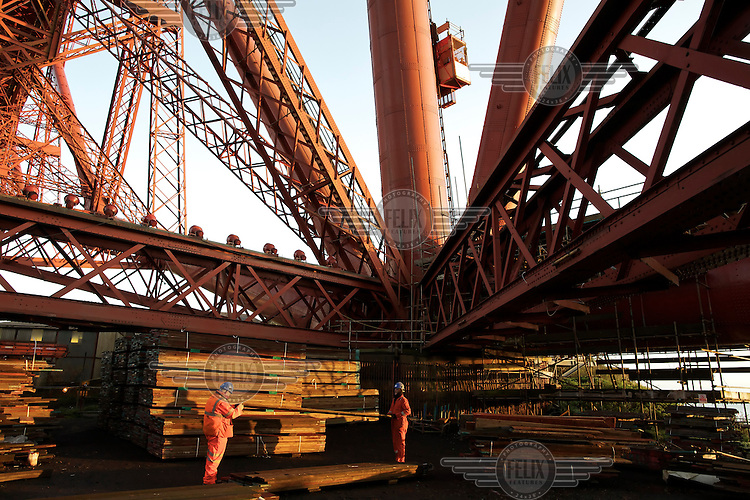 Materials waiting to be moved offsite by road transport. The 125 year old Forth Rail Bridge spans the river Forth near Edinburgh. Network Rail, the operator of the rail track that leads over the bridge, has spent 10 years and GBP 130 million repainting the 230,000 square metres of steel and 6.5 million rivets on the bridge. The iconic red paint used on the bridge is made to match the red-oxide paint used over 100 years ago. The bridge will now need no further painting for at least 20 years.