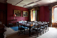 The traditional dining room has burgundy red walls and curtain pelmets shaped to reflect the gothic windows