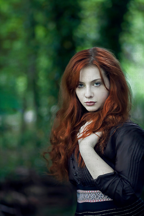 Young girl with red hair alone in the forest.