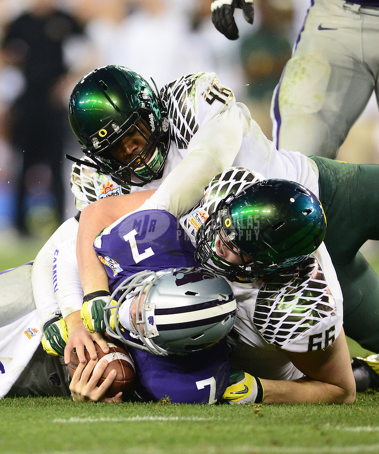 Jan. 3, 2013; Glendale, AZ, USA: Kansas State Wildcats quarterback Collin Klein (7) is tackled by Oregon Ducks linebacker Michael Clay (46) and defensive tackle Taylor Hart (66) in the second half during the 2013 Fiesta Bowl at University of Phoenix Stadium. Oregon defeated Kansas State 35-17. Mandatory Credit: Mark J. Rebilas-