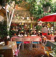 Tables, with colourful tablecloths, and white metal chairs are placed on an outside terrace area of a restaurant.