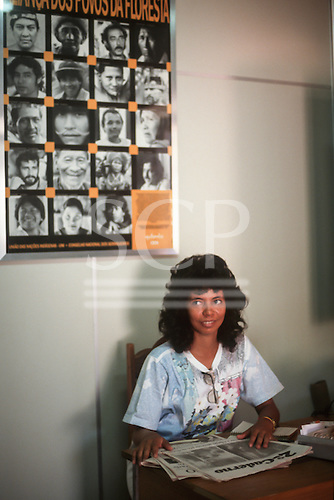 Rio Branco, Acre, Brazil. Woman reading the newspaper in the office of the CNS - Conselho Nacional de Seringueiros, National Rubber Tappers' Council.