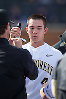 Stuart Fairchild (4) of the Wake Forest Demon Deacons is congratulated by teammates after scoring a run against the Miami Hurricanes at Wake Forest Baseball Park on March 21, 2015 in Winston-Salem, North Carolina.  The Hurricanes defeated the Demon Deacons 12-7.  (Brian Westerholt/Four Seam Images)