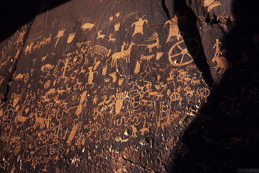 "Innumerable petroglyphs mark Newspaper Rock, near Canyonlands National Park in Utah. This is perhaps the most highly visited rock art site in Utah and certainly one of the most elaborate. Petroglyphs are pecked into the rock, usually through a darkly patinated surface, to reveal the lighter rock below. Hundreds of figures have been created here during both prehistoric and historic times but are primarily Anasazi of the Abajo-La Sal style. The most recent Ute-style contributions include the horse and rider. The Navajo name for this site is Tse Hane, meaning ""rock that tells a story."" Located along a pre-historic travel corridor and perennial stream which flows off the Abajo Mountains to the south, thousands of people must have passed this way over the ages. Many of these people obviously paused to add their contribution to this slab of Wingate sandstone."