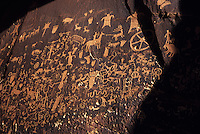 """Innumerable petroglyphs mark Newspaper Rock, near Canyonlands National Park in Utah. This is perhaps the most highly visited rock art site in Utah and certainly one of the most elaborate. Petroglyphs are pecked into the rock, usually through a darkly patinated surface, to reveal the lighter rock below. Hundreds of figures have been created here during both prehistoric and historic times but are primarily Anasazi of the Abajo-La Sal style. The most recent Ute-style contributions include the horse and rider. The Navajo name for this site is Tse Hane, meaning """"rock that tells a story."""" Located along a pre-historic travel corridor and perennial stream which flows off the Abajo Mountains to the south, thousands of people must have passed this way over the ages. Many of these people obviously paused to add their contribution to this slab of Wingate sandstone."""