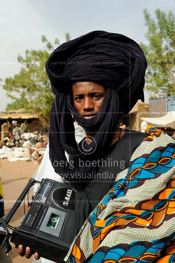 MALI, young Peulh man with black turban and X-bass radio cassette player, Fulani people / Mali, junger Peulh Mann mit Turban und Radio, Fulbe Hirtenvolk
