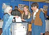 New Carrollton, MD - January 29, 2005 -- Election workers Emily Hearn, center, and Mehdi Sindr, right, help a voter who declined to be identified, left, cast her ballot in the Iraqi election in New Carrollton, Maryland on January 29, 2005..Credit: Ron Sachs / CNP..(RESTRICTION: NO New York or New Jersey Newspapers or newspapers within a 75 mile radius of New York City)
