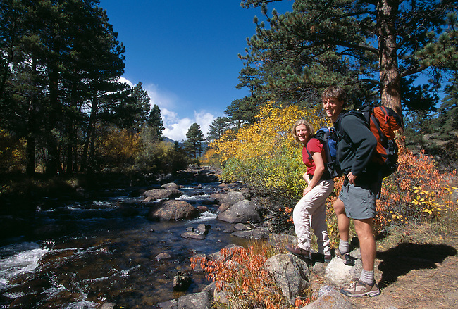 Young couple stands along river's edge surrounded by fall color, Rocky Mtn Nat'l Park, CO