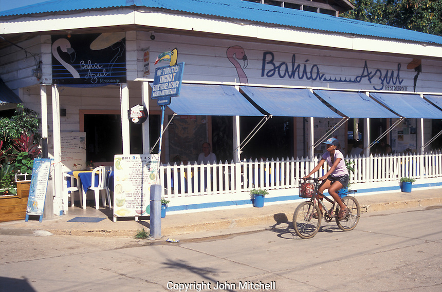 Young black woman riding a bicycle past the Bahia Azul restaurant in the town of Livingston on the Caribbean coast of Guatemala