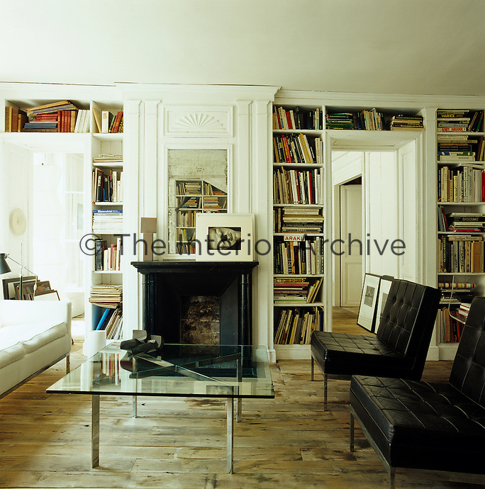 View of the library looking towards the Directoire fireplace with a mirrored panel and photograph by Raoul Haussman on the mantelpiece
