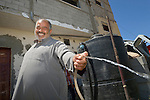 Akram Abudagga sprays water he collected in a rainwater harvesting system he installed at his home in Al Fukari, Gaza. He had a system before which he built to irrigate his small farm, but Israeli air strikes in 2014 destroyed that system and damaged his house. With help from Diakonie Katastrophenhilfe, a member of the ACT Alliance, he rebuilt the water system and has repaired some of the damage to his home. In the wake of the devastating 2014 war, ACT Alliance members are supporting health care, vocational training, rehabilitation of housing and water systems, psycho-social care, and other humanitarian actions throughout the besieged Palestinian territory.