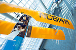 Cradle of Aviation Museum, Garden City, New York, January 20 2010. 1929 Fleet biplane is dramatically suspended in a 60 degree bank between the second-to-third floor stair landing and the glass atrium wall. In this location, the visitor on the stairs has the unusual vantage of looking right into the two open cockpits. http://www.cradleofaviation.org/exhibits/atrium/index.html