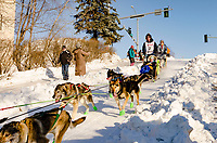 Ryan Redington and team run past spectators and down the Cordova Street hill with an Iditarider in the<br /> basket and a handler during the Anchorage, Alaska ceremonial start on Saturday March 4th<br /> during the 2017 Iditarod race. Photo &copy;2017 by Kristie Lent/ SchultzPhoto.com