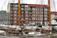 Wooden Schooner in the Port in a Danish City, with the City architecture and Cars in the background.