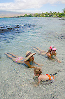 A local boy with his mother and her friend play in a tide pool at a beach in Puako, South Kohala, Island of Hawai'i.