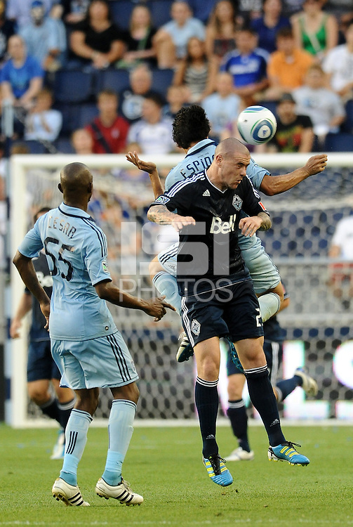 Roger Espinoza (light blue) Sporting KC goes up for  aheader with Eric Hassli Vancouver Whitecaps... Sporting KC defeated Vancouver Whitecaps 2-1 at LIVESTRONG Sporting Park, Kansas City, Kanas.