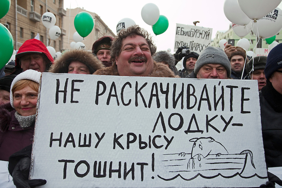 """Moscow, Russia, 04/02/2012..Satirical novelist Dmitry Bykov holds a poster reading """"Don't rock the boat - our rat is sick"""",  as tens of thousands of demonstrators march in central Moscow and protest against election fraud and Prime Minister Vladimir Putin in temperatures of -20 centigrade. Organisers claimed an attendance of 130,000 despite the bitter cold."""