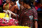 woman looking flowers  at  Devaraja Market in Mysore