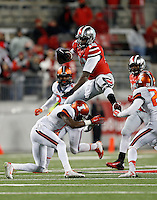 Ohio State Buckeyes quarterback Cardale Jones (12) hurdles over Illinois Fighting Illini defensive back Jevaris Little (15) as he keeps the ball in the fourth quarter the college football game between the Ohio State Buckeyes and the Illinois Fighting Illini at Ohio Stadium in Columbus, Saturday night, November 1, 2014. The Ohio State Buckeyes defeated the Illinois Fighting Illini 55 - 14. (The Columbus Dispatch / Eamon Queeney)