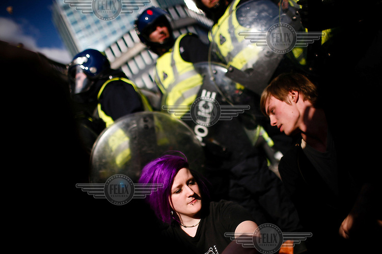 Demonstrators sit in front of riot police as thousands of protestors descended on the City of London ahead of the G20 summit of world leaders to express anger at the economic crisis, which many blame on the excesses of capitalism.