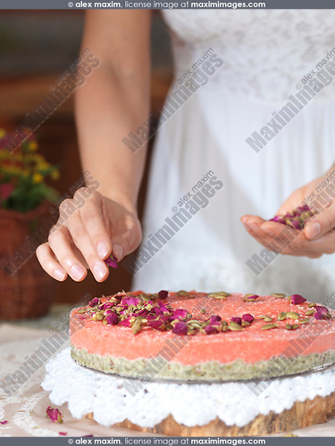 Closeup of woman hands decorating a home-made fruit cake with rose buds at home