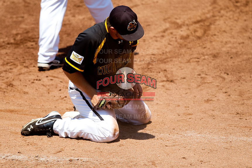 Albert Minnis (33) of the Wichita State Shockers sits in the dirt after diving head first into first base to get an out during a game against the Missouri State Bears in the 2012 Missouri Valley Conference Championship Tournament at Hammons Field on May 23, 2012 in Springfield, Missouri. (David Welker/Four Seam Images)