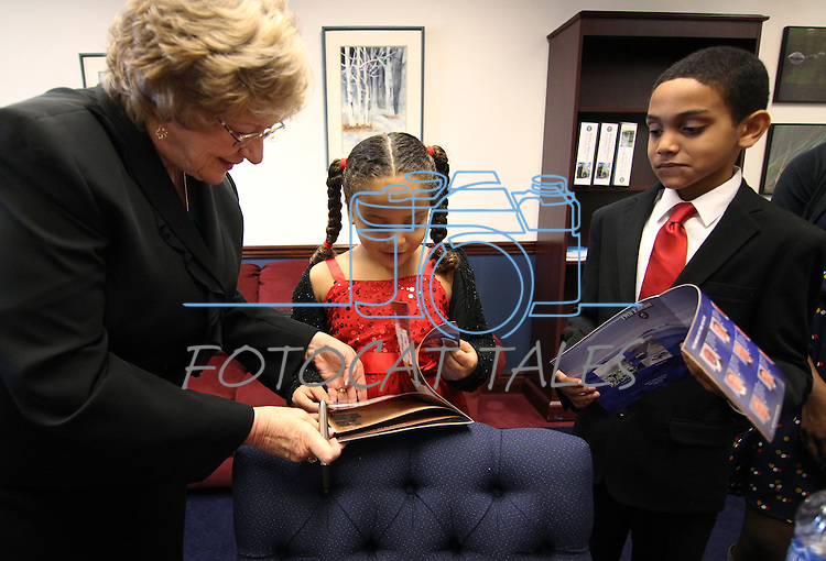 Nevada Sen. Joyce Woodhouse, D-Henderson, autographs the Legislature Guide for Chloe Horne, 7 and her brother Henry, 9 before opening day ceremonies at the 77th Legislative Session in Carson City, Nev. on Monday, Feb. 4, 2013. (AP Photo/Cathleen Allison)