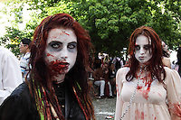 Male Zombie with dreadlock looking at the camera, wearing black shirt, holding the chain to the female zombie in the back, wearing a white dress with blood on. In background trees, visitors to the event and other zombies