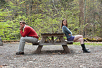 Young couple having a disagreement, sitting at picnic table