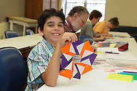 A young origami folder learns how to crease Mette Pederson's Foil Ring in a morning class at the OrigamiUSA 2013 Convention.