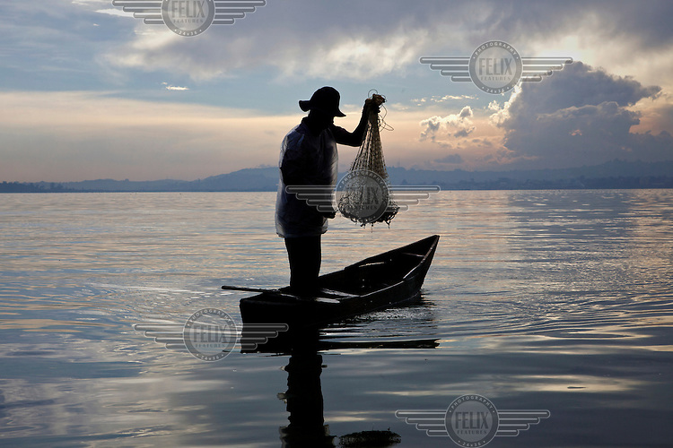 A fisherman get his net ready to be thrown from his pirogue onto Lake Victoria early in the morning near Kampala.