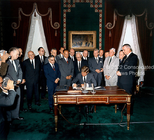 United States President John F. Kennedy signs the Limited Nuclear Test Ban Treaty in the White House Treaty Room on October 7, 1963. From left to right: William Hopkins, U.S. Senator Mike Mansfield (Democrat of Montana), John J. McCloy, Adrian S. Fisher, U.S. Senator John Pastore (Democrat of Rhode Island), W. Averell Harriman, U.S. Senator George Smathers (Democrat of Florida), U.S. Senator J.W. Fulbright (Democrat of Arkansas), U.S. Secretary of State Dean Rusk,  U.S. Senator George Aiken (Republican of Vermont), President Kennedy, U.S. Senator Hubert H. Humphrey (Democrat of Minnesota),  U.S. Senator Everett Dirksen (Republican of Illinois), William C. Foster, U.S. Senator Howard W. Cannon (Democrat of Nevada), U.S. Senator Leverett Saltonstall (Republican of Massachusetts), U.S. Senator Thomas H. Kuchel (Republican of California), U.S. Vice President Lyndon B. Johnson. White House, Treaty Room. .Credit: Robert Knudsen - White House via CNP