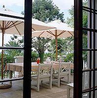 This outdoor eating area beneath cotton parasols is screened from the neighbours by palms and mature trees