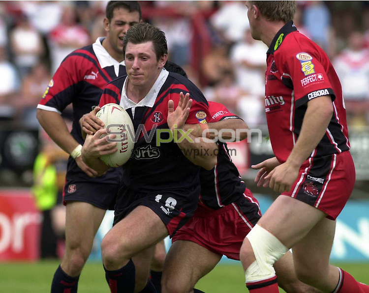 .PICTURE BY :Chris Whiteoak/SWpix.com. Rugby Super League, Salford City Reds v St Helens, Salford, 8/8/2004..?COPYRIGHT PICTURE>>SIMON WILKINSON>>0870 0920092>>..St Helens' John Stankevitch is tackled by Salford's Kevin McGuinness