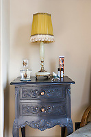 A vintage bedside table has been painted a deep pewter grey in a pleasing contrast to the saffron-yellow shade of the bedside lamp