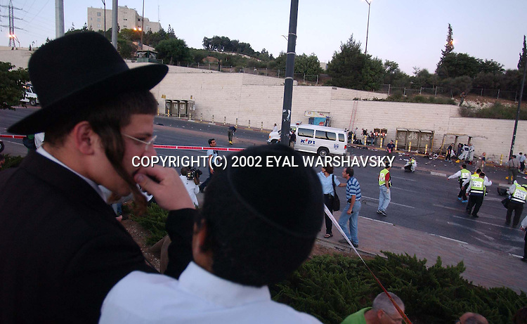 Ultra orthodox youths watch  rescue workers and police forensic volunteers search the site of a suicide bombing in Jerusalem Wednesday June 19 2002. A suicide bomber exploded at a bus station wednesday killing seven and wounding 40 Photo by Eyal Warshavsky