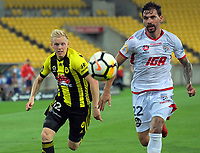 Wellington's Adam Parkhouse and Adelaide's Ersan Gulum chase the ball during the A-League football match between Wellington Phoenix and Adelaide United at Westpac Stadium in Wellington, New Zealand on Saturday, 27 January 2018. Photo: Dave Lintott / lintottphoto.co.nz