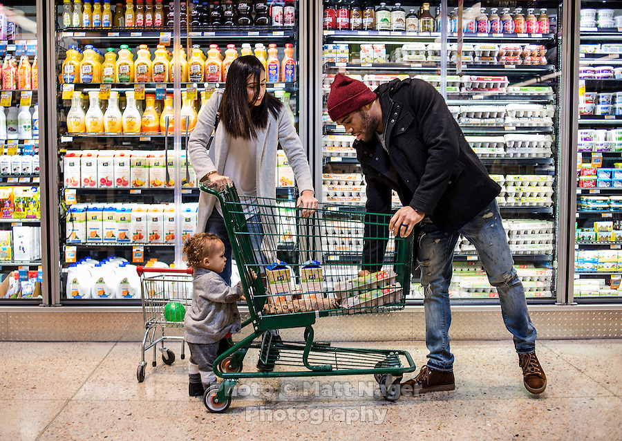 Olympic Gold champion wrestler Jordan Burroughs (cq) with his wife Lauren Mariacher (cq) and their son Beacon Burroughs (cq, age 19 months) shopping at Whole Foods in Lincoln, Nebraska, Friday, February 12, 2015. Burroughs is training for the upcoming 2016 olympic games in Rio de Janeiro, Brazil where he hopes to win another gold medal. <br /> <br /> Photo by Matt Nager