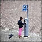 Nederland, Amsterdam, 01-02-2011-  Vrouw bij parkeerautomaat. Ze lijkt moeite te hebben met de werking van het apparaat.Ze lijkt er af en toe vertwijfeld bij te staan en het duurt allemaal erg lang.Het lukt uiteindelijk niet om een kaart te verkrijgen. FOTO: Gerard Til / Hollandse Hoogte