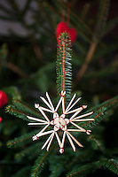Detail of a delicate straw star from IKEA hanging on a Christmas tree