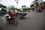 Bicycles, rickshaws and motorbikes go through a traffic circle one late afternoon in Nha Trang, Vietnam. July 13, 2011.