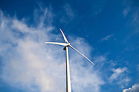 Wind turbine rises into cloudy blue sky