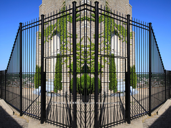 A Contrived Image, A Symmetrical Vine Covered Stone Building inside Of A Black Metal Fence On A Sunny Day