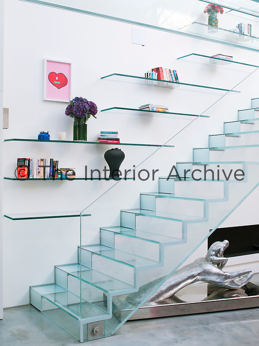 Open shelving on the staircase wall displays a few select books and vases, keeping clutter to a minimum
